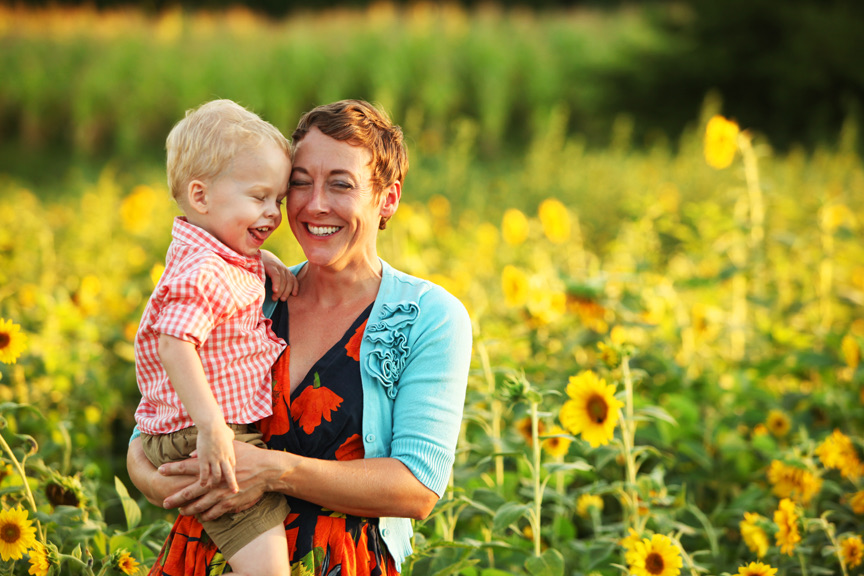 A woman holding a child in a field of sunflowers.