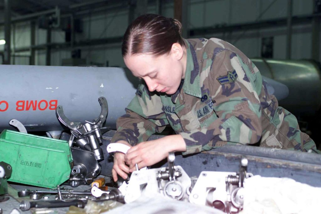 A woman in an Air Force uniform working on some machinery.