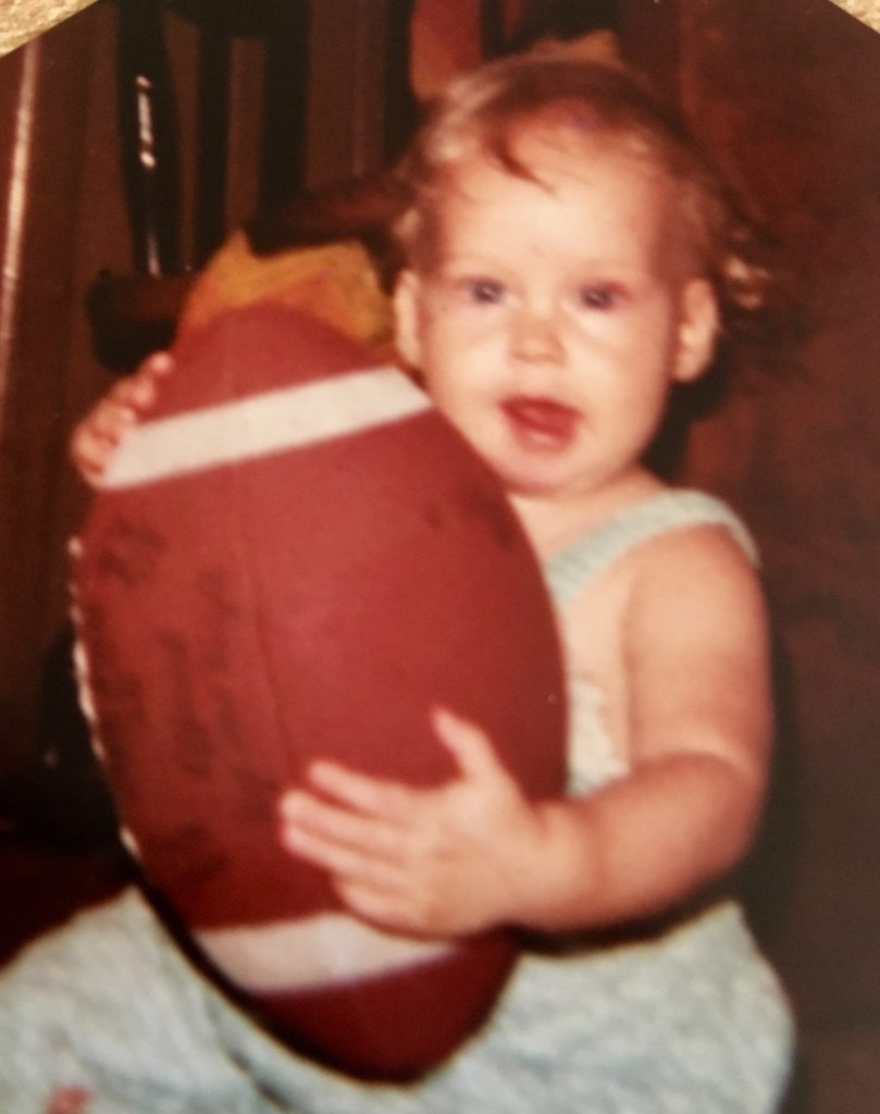 A baby holding a football.