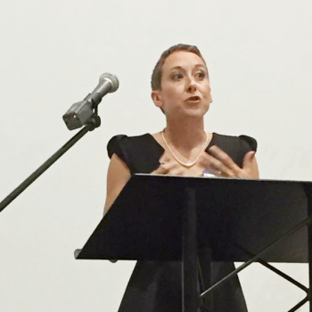 Woman in front of a podium talking into a microphone.